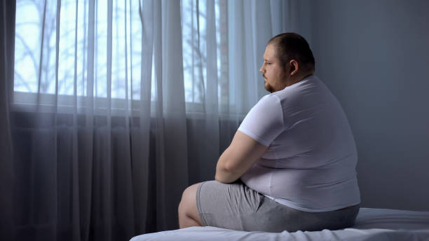 depressed fat man sitting on bed at home, worried about overweight, insecurities - obesity foto e immagini stock