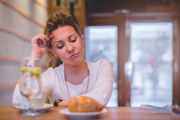 Depressed female at restaurant with broken heart She is 34 years old business woman. Stressed out from work and bad relationship. Sitting at her favorite cafe shop and trying to relax one mid adult woman only stock pictures, royalty-free photos & images