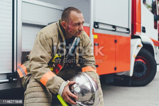 Unhappy firefighter sitting at the truck after rescue operation. Real firefighter at work.