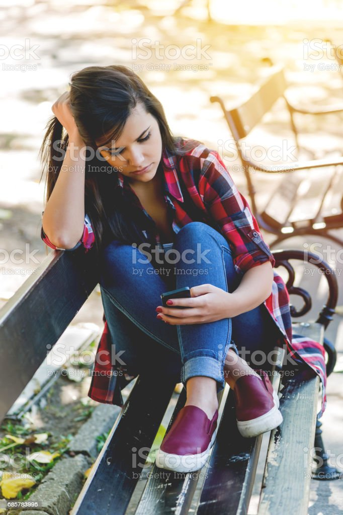 Depressed girl read messages in the park royalty-free stock photo
