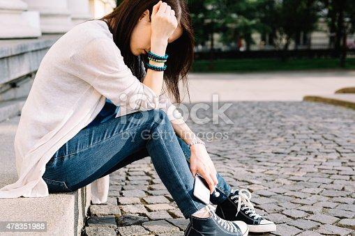 istock Depressed girl sitting at the street 478351988