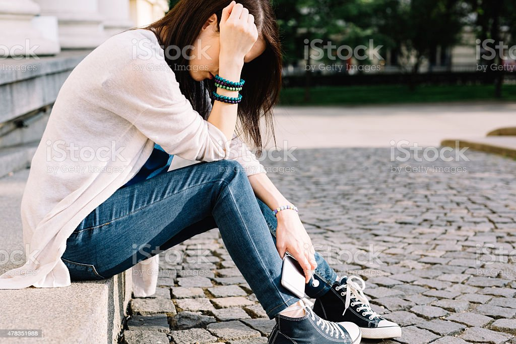 Depressed girl sitting at the street stock photo