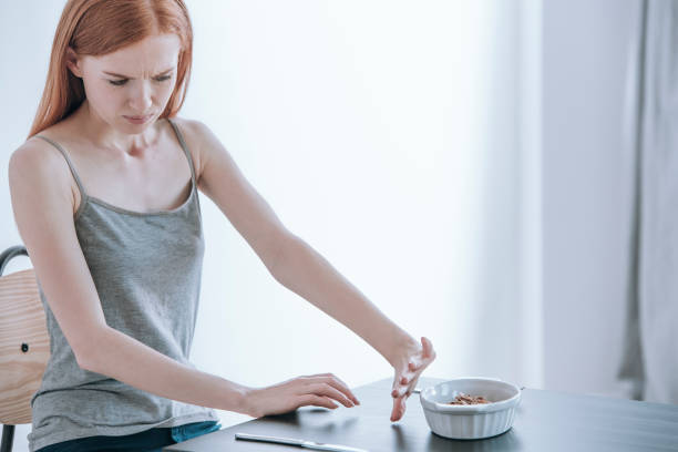 Depressed girl with eating disorder Young depressed girl at table with food in bowl. Eating disorders concept anorexia nervosa stock pictures, royalty-free photos & images