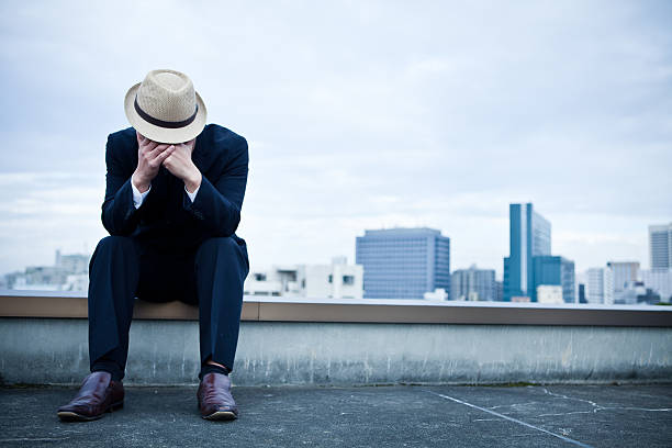 Depressed Japanese businessman on a roof stock photo