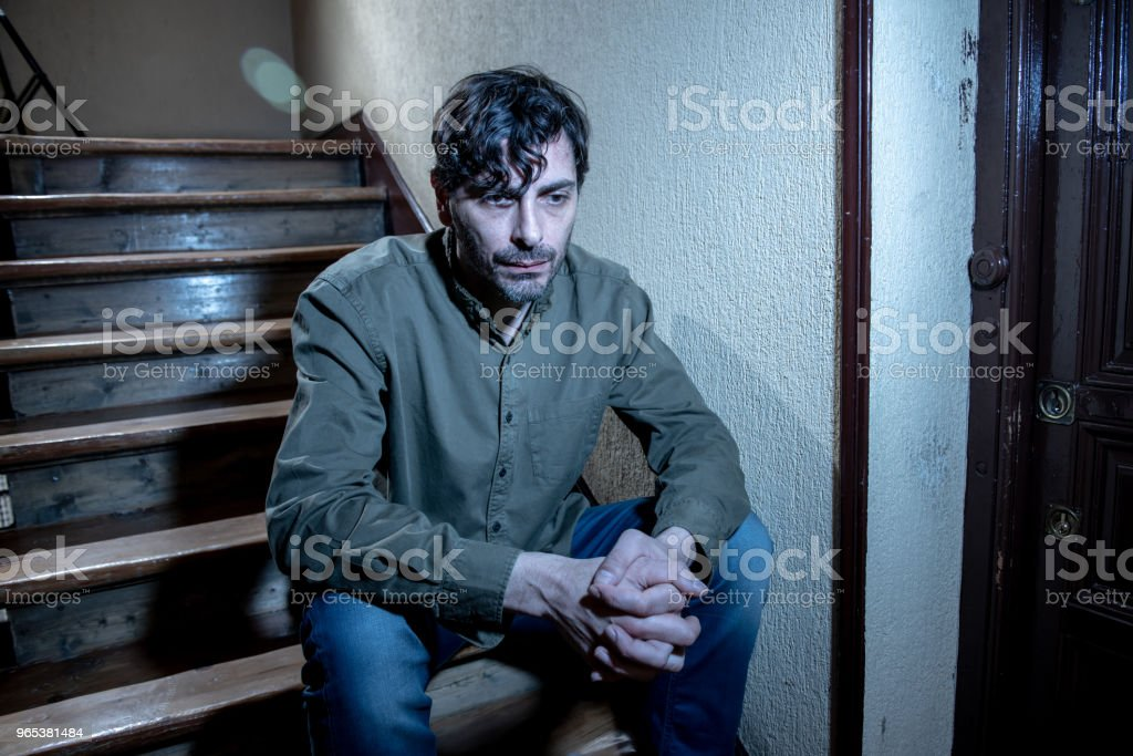 depressed latin man sitting head in hands inside in a stairwell feeling lonely and sad and stressed about work and life in a mental health concept zbiór zdjęć royalty-free