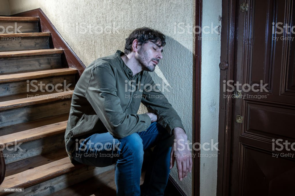 depressed latin man sitting head in hands inside in a stairwell feeling lonely and sad and stressed about work and life in a mental health concept royalty-free stock photo