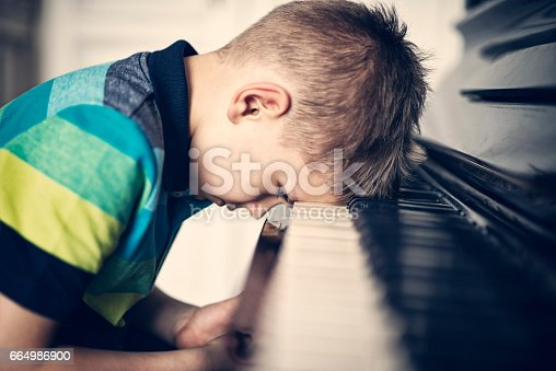 istock Depressed little boy frustrated with his piano lesson 664986900
