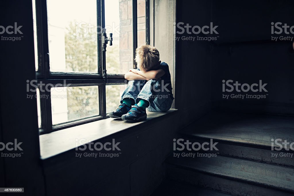 Depressed little boy in old staircase stock photo