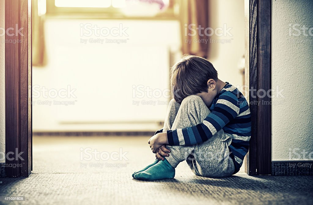 Depressed little boy sitting on the floor royalty-free stock photo