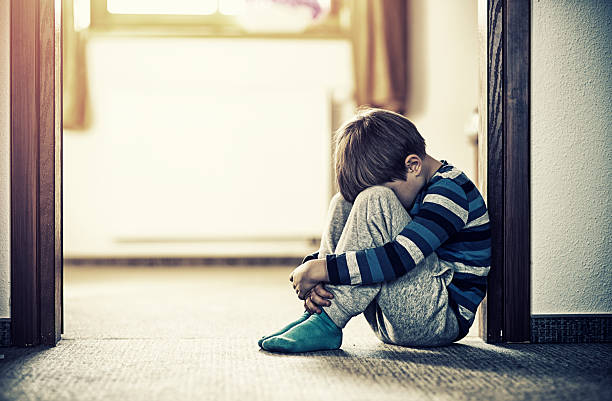 Depressed little boy sitting on the floor stock photo