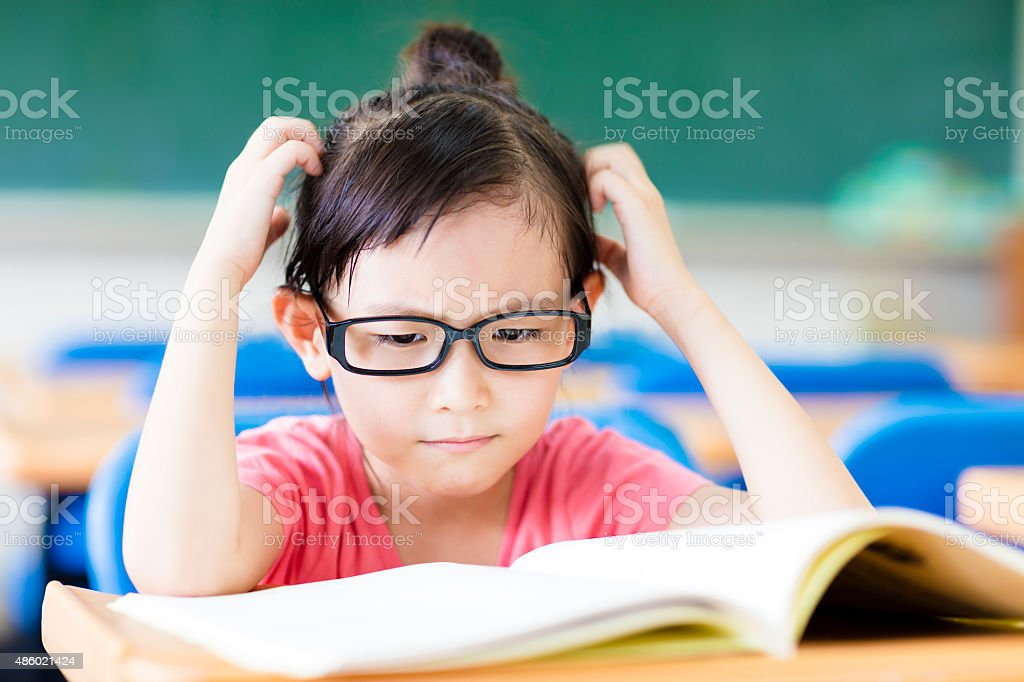 Depressed little girl study in the classroom stock photo