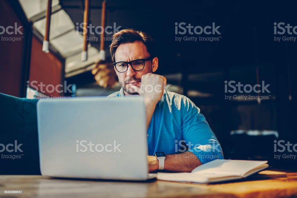 Depressed male entrepreneur feeling headache can't solve problems with finance checking report on netbook.Stressed manager worried about documentation on laptop failure with saving on software royalty-free stock photo