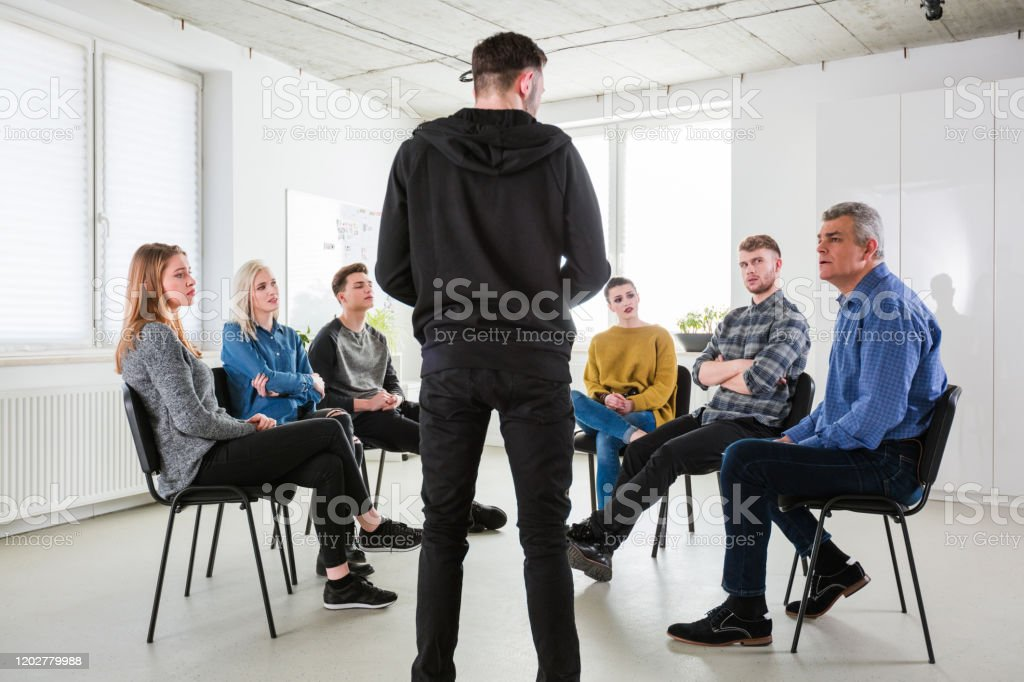Depressed male sharing problems during meeting Depressed male sharing problems during meeting. Social worker and university students are in group therapy. They are having mental health session in lecture hall. 18-19 Years Stock Photo