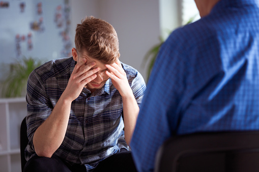 Depressed Male With Head In Hand During Therapy Stock Photo - Download Image Now