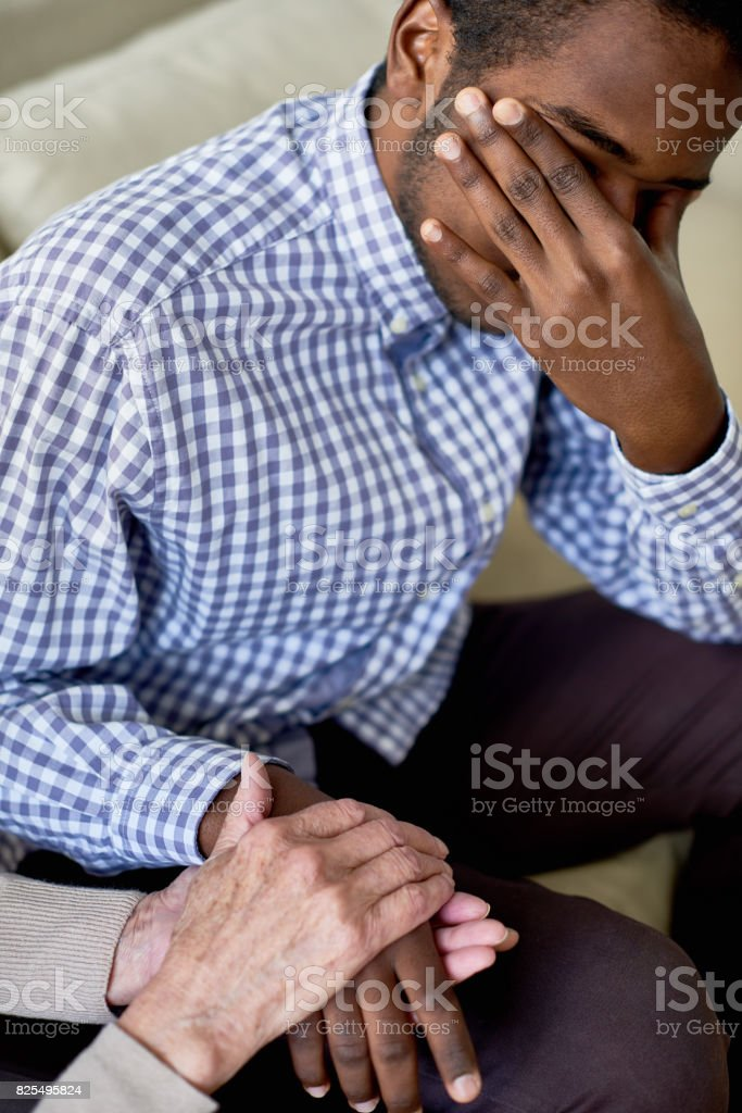 Depressed man being consoled by therapist stock photo