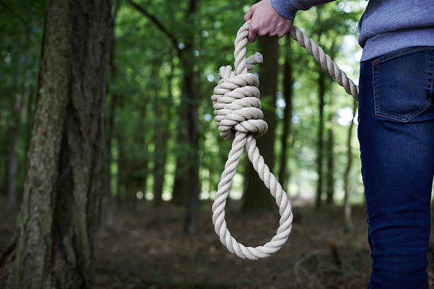 depressed man contemplating suicide by hanging in forest - noose stock photos and pictures