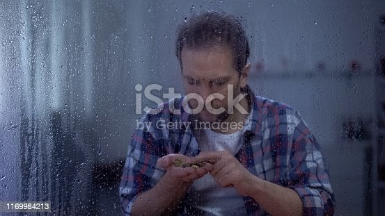 Depressed man counting coins behind rainy window, low incomes, poverty concept