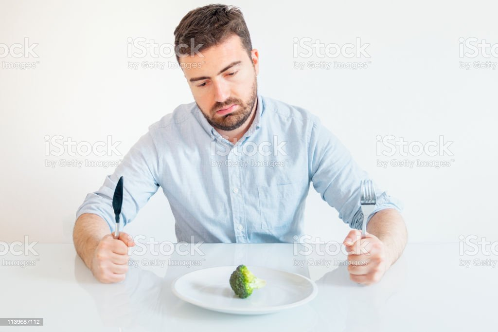 Sad and hungry man watching poor diet meal