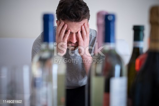 Alcohol addicted man portrait alone with spirit bottle