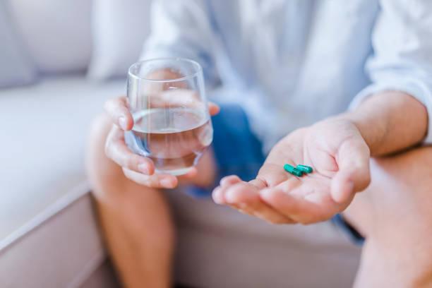 depressed man holds antidepressant meds - prescription meds stock pictures, royalty-free photos & images
