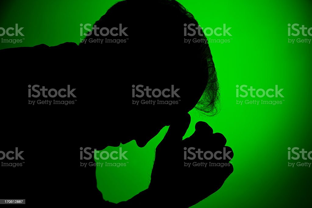 Depressed man in silhouette on green royalty-free stock photo