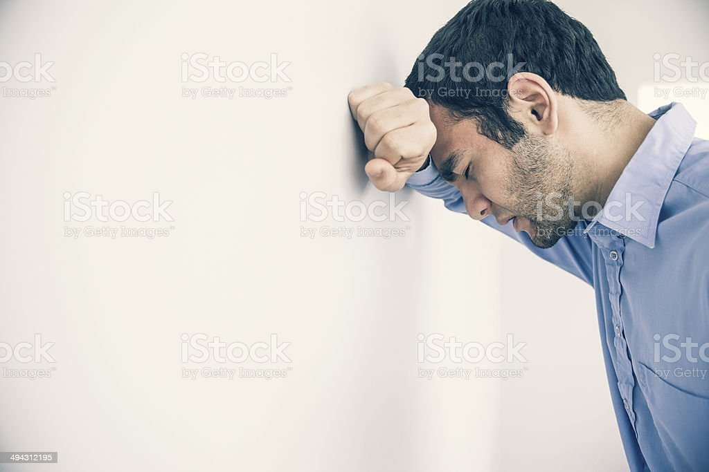 Depressed man leaning his head against a wall stock photo