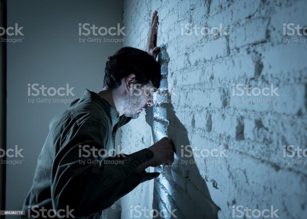 deprimiert Mann gelehnt auf einer weißen Wand im dunklen Raum zu Hause traurig, müde und besorgt in einem psychischen Depression Konzept. - Lizenzfrei Angst Stock-Foto