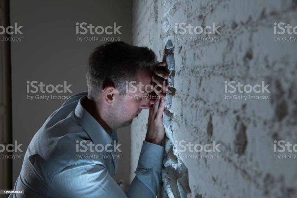 우울한 남자 어두운 방에서 집에서 흰 벽에 기대어 슬픈, 피곤 하 고 정신 건강 우울증 개념에 불안을 느낌. - 로열티 프리 걱정하는 스톡 사진