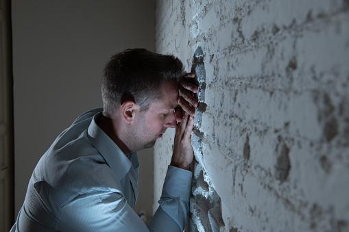 우울한 남자 어두운 방에서 집에서 흰 벽에 기대어 슬픈 피곤 하 고 정신 건강 우울증 개념에 불안을 느낌 걱정하는에 대한 스톡 사진 및 기타 이미지