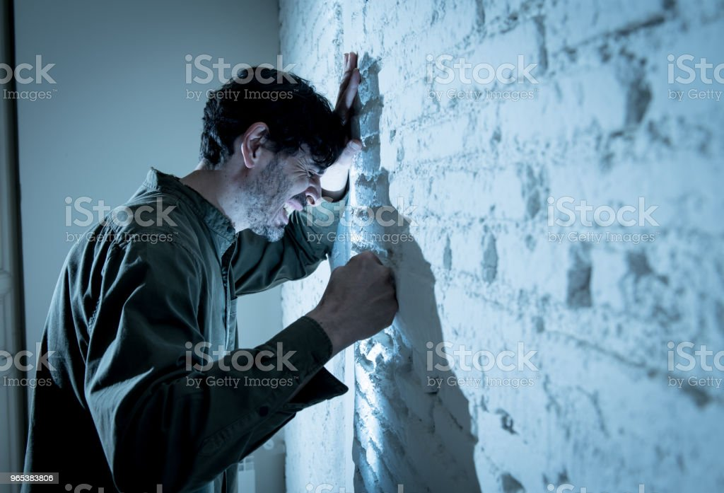 depressed man leaning up on a white wall in dark room at home, feeling sad, tired and anxious in a mental health depression concept. royalty-free stock photo
