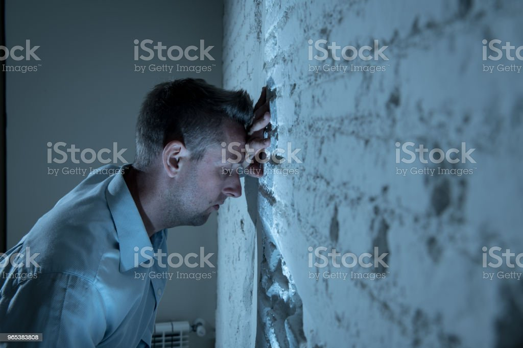 depressed man leaning up on a white wall in dark room at home, feeling sad, tired and anxious in a mental health depression concept. zbiór zdjęć royalty-free