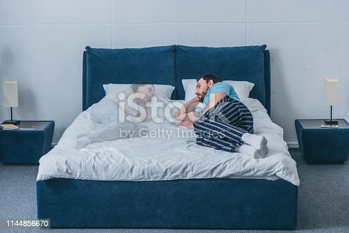 depressed man lying in bed and looking at wife ghost