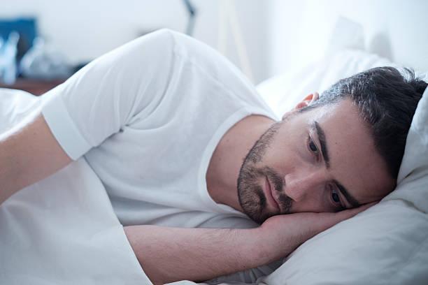 Depressed man lying in his bed and feeling bad stok fotoğrafı