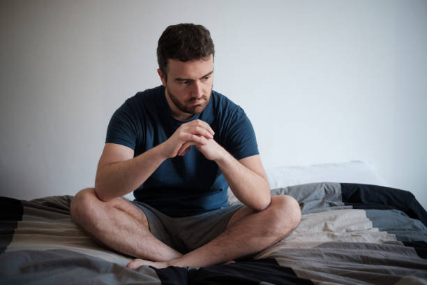 Depressed man seated on his bed feeling bad stock photo