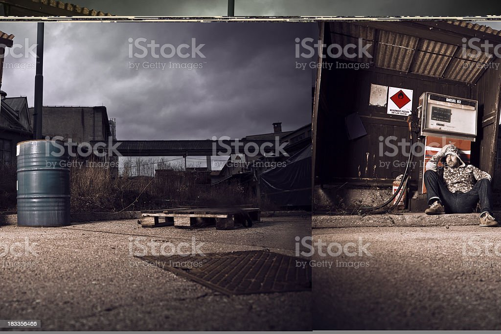 Depressed man sitting at abandoned gas station royalty-free stock photo