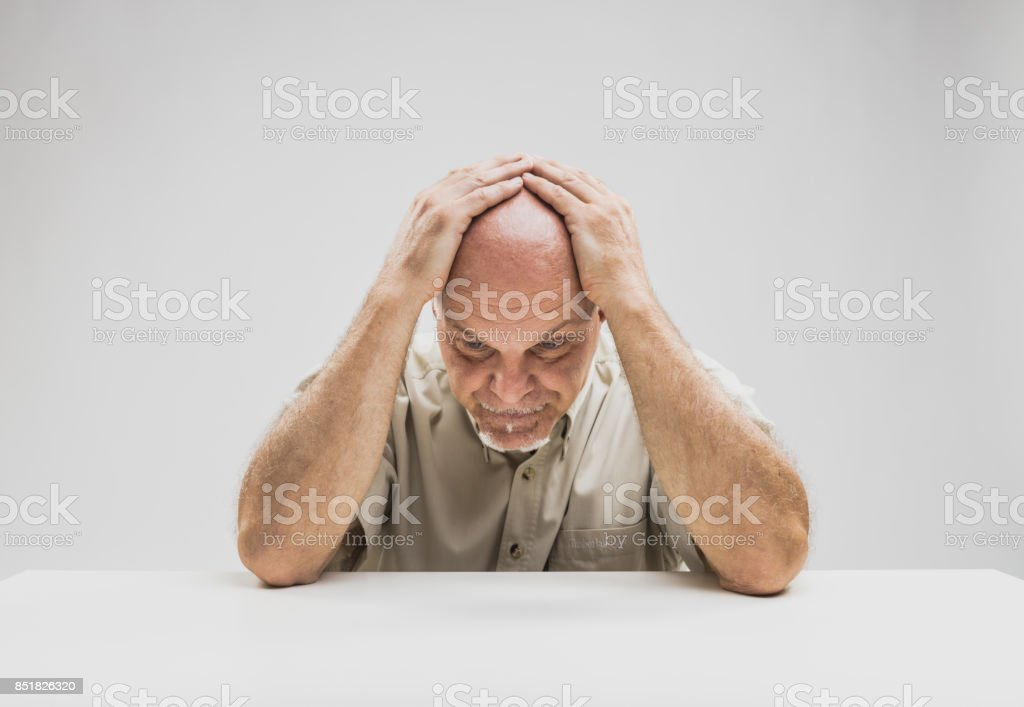 Depressed man sitting at table stock photo