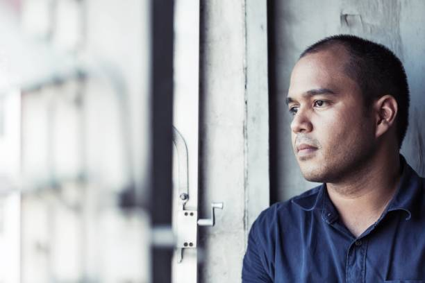 depressiver mann sitzt im dunklen raum - besorgt stock-fotos und bilder