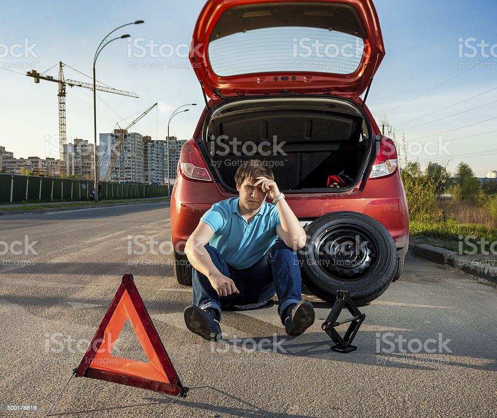 depressed man sitting near car with punctured tire stock photo