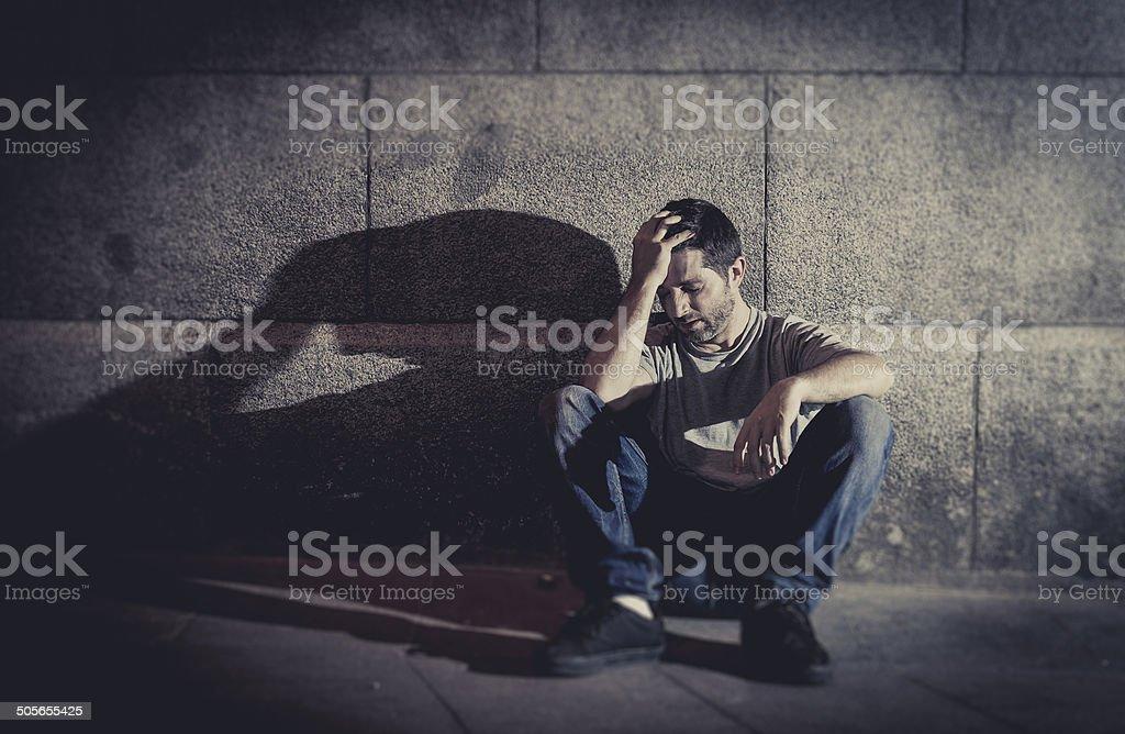 depressed man sitting on street ground with shadow stock photo