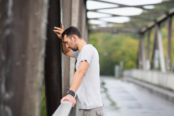 Depressed Man standing on bridge looking down stock photo