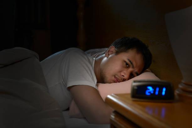 Depresif adam yatakta yatan uykusuzluk acı stok fotoğrafı