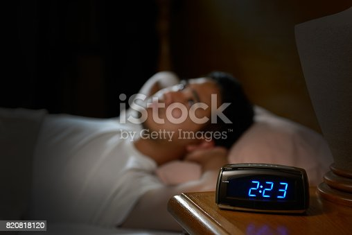 istock Depressed man suffering from insomnia lying in bed 820818120