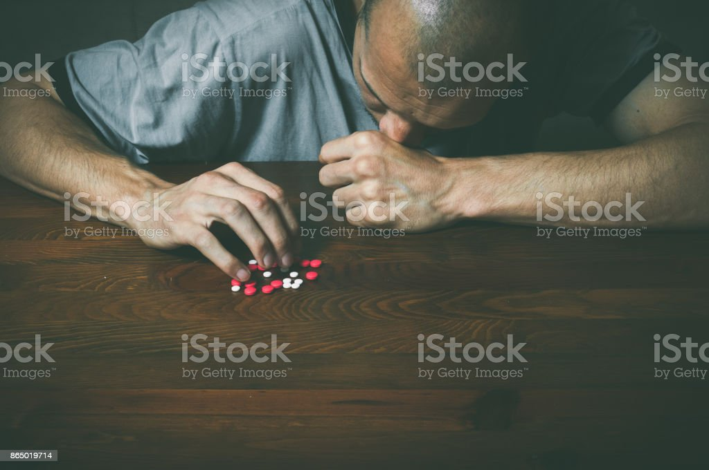 Depressed man suffering from suicidal depression want to commit suicide by taking strong medicament drugs and pills Depressed man suffering from suicidal depression want to commit suicide by taking strong medicament drugs and pills Abandoned Stock Photo