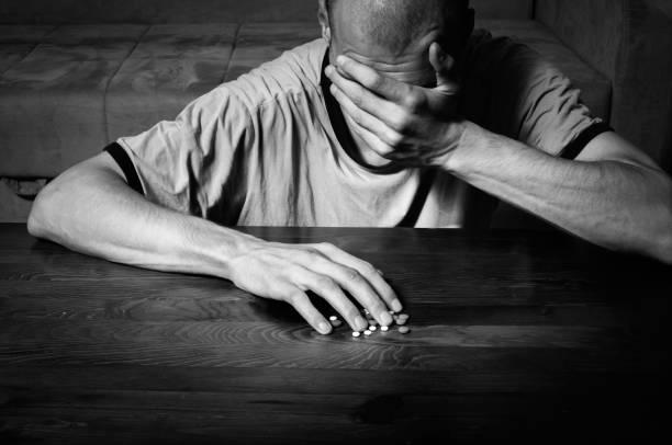 그는 그의 암실 흑백 이미지의 바닥에 앉아 하는 동안 강한의 약 마약 및 환 약을 복용 하 여 자살을 원하는 우울된 사람 자살 우울증에서 고통 - 마약 남용 뉴스 사진 이미지