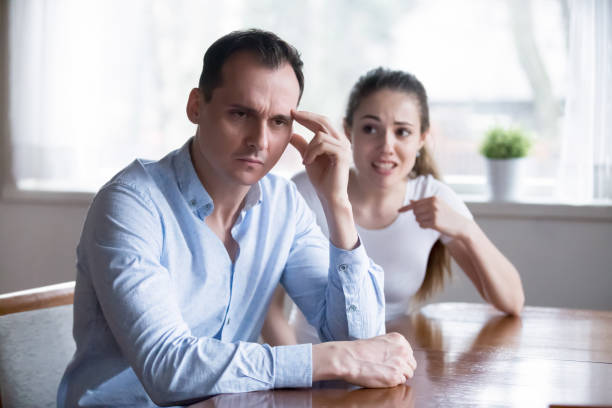 Depressed man turn back ignoring angry screaming woman Couple in fight, man in focus. Depressed husband with headache ignoring screaming irritated woman. Big trouble, problem because of misunderstanding, conflict in family. Hard relationship concept former stock pictures, royalty-free photos & images