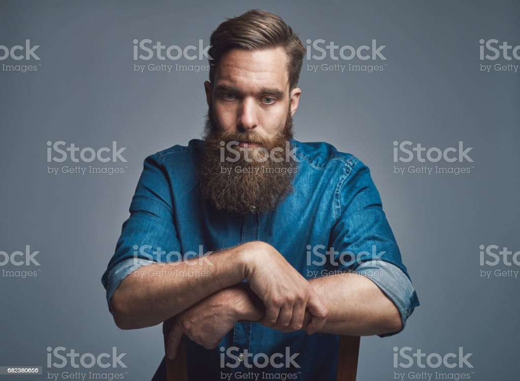 Depressed man with arms on back of chair over gray royalty-free stock photo