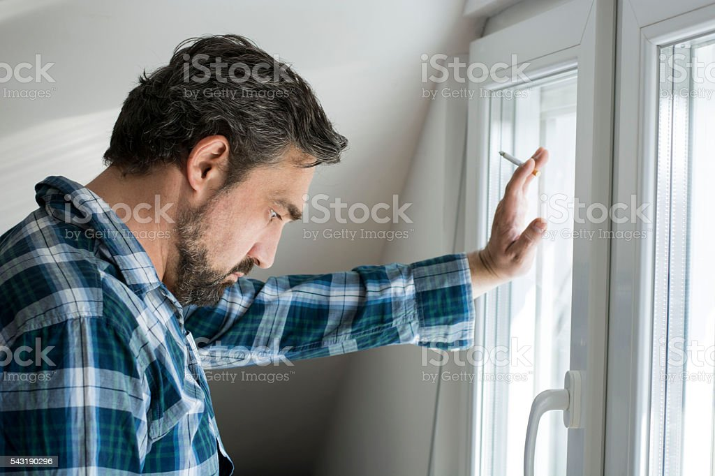 Depressed man with cigarette standing besides window stock photo