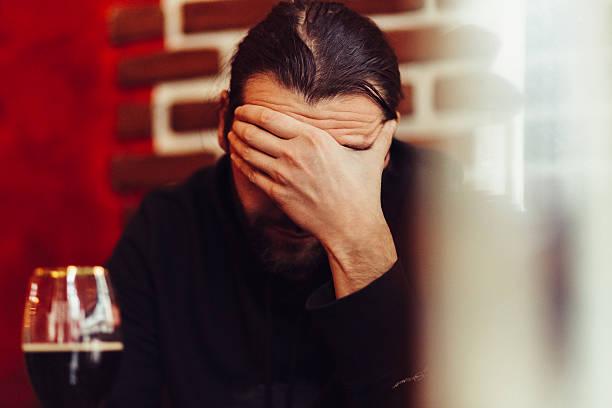 ein deprimierter mann mit hand auf gesicht - migräne vorbeugen stock-fotos und bilder