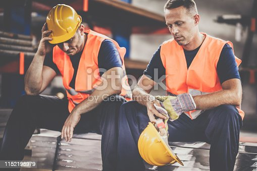 Mid adult metal workers received bad news while resting in aluminum mill.