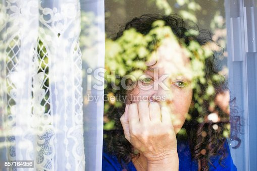 543048812 istock photo Depressed mature Caucasian female looking out of a window 857164956